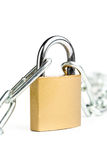 Brass padlock connecting two chains over white background Royalty Free Stock Photos