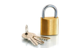 Brass Padlock and Keys. On a white reflective surface stock image