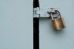 Brass padlock on painted door Stock Photography