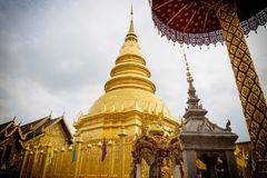 The brass pagoda is glittering inside Wat Phra That Hariphunchai. Woramahawihan Stock Photo