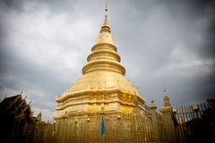 The brass pagoda is glittering inside Wat Phra That Hariphunchai. Woramahawihan Stock Photography