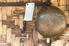 Brass pan and chopping knife hanging on the woven bamboo wall Royalty Free Stock Photo