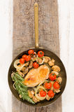 Brass pan with fried chicken breast filet and vegetables Royalty Free Stock Photos