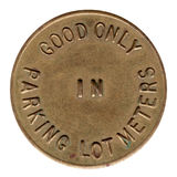 Brass Parking Meter Token. Antique brass parking meter token from the 1950's.  Good only in parking lot meters Royalty Free Stock Photos