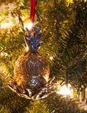 A brass pineapple Christmas ornament on a tree with silver accents. A pineapple Christmas ornament on a fur tree with blurred lights in the background with royalty free stock photography