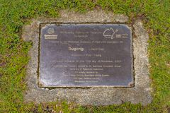 Brass plaque identifying solid marble Dugong Sculpture, hand carved by Foot Young. Sculpture to mark the centenary of federation in the Whitsundays. 2001. From royalty free stock photo
