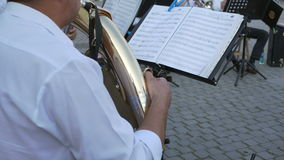 Brass Player Follows Music Sheets. Musician is performing along the band with the Baritone horn, following the music sheets, somewhere outdoor. The baritone horn stock video footage