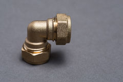 Brass plumbing compression fittings on grey table Royalty Free Stock Image