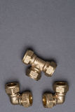 Brass plumbing compression fittings on grey table Stock Photography