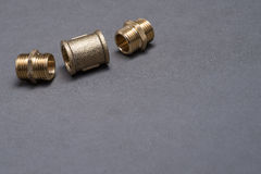 Brass plumbing fittings on grey table Stock Photography