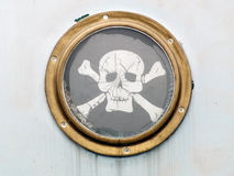 Brass porthole on ship with pirate flag Royalty Free Stock Images