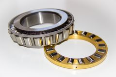 Brass roller cage of a thrust roller bearing and stainless roller cage of a tapered roller bearing. With selective focus Royalty Free Stock Images