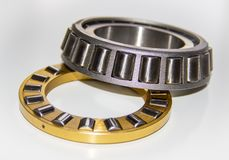 Brass roller cage of a thrust roller bearing and stainless roller cage of a tapered roller bearing. With selective focus Stock Photography