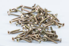 Brass screws resting on white surface Royalty Free Stock Photography