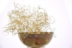 Brass shavings in a metalic bowl Stock Photo