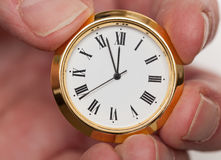 Brass small watch or clock in fingers Stock Images