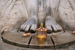 Brass statue infront of a gigiantic monolithic statue of Bahubali, also known as Gomateshwara, Vindhyagiri Hill, Shravanbelgola. Karnataka stock photo