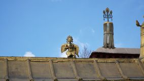 Brass statue on the roof with sky. On the building Royalty Free Stock Image