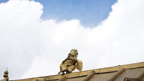 Brass statue on the roof with sky. On the building Royalty Free Stock Photo