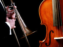 Brass and stringed instruments. Brass and stringed symphony musical instruments shown on black, featuring a concert trombone and violin or cello Stock Images