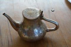 Brass tea pot. Oriental brass tea pot on a wooden table Royalty Free Stock Photo