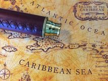Brass telescope and map II. Leather wrapped brass telescope on vintage-style old world Caribbean map royalty free stock photography