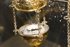Brass thurible liturgy censer with burning incense in it. Christian Church brass thurible liturgy censer with coal, ash, smoke and incense in it. Closeup stock photos