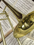 Brass Trombone and Classical Music 5b. Brass trombone laid across classical music in the background Stock Photos