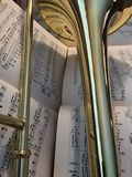 Brass Trombone and Classical Music 398 edit. Brass trombone laid across classical music in the background Royalty Free Stock Photography