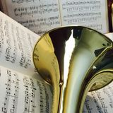 Brass Trombone and Classical Music 6. Brass trombone laid across classical music in the background Royalty Free Stock Photo