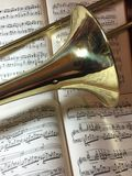 Brass Trombone and classical music 9. Brass trombone laid across classical music and synthesizer keyboard in the background Royalty Free Stock Images