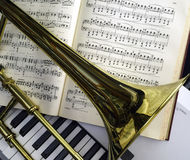 Brass Trombone and classical music laid over synthesizer keyboard. Brass trombone laid across classical music and synthesizer keyboard in the background Royalty Free Stock Images