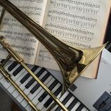 Brass Trombone and synthesizer keyboard and classical music. Brass trombone laid across classical music and synthesizer keyboard in the background royalty free stock image