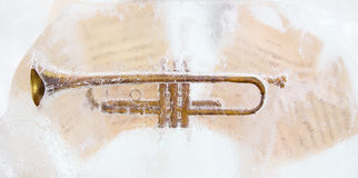 Brass trumpet and sheet music. Brass trumpet and sheet music frozen into the ice Stock Images