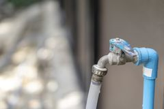 Brass water tap with rubber tube stock images