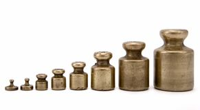 Brass weight. Different vintage brass weights unit standing in one row (from 1g to 200g) on white background royalty free stock images
