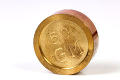 Brass weight. Beautiful shot of 50gm brass weight on white background royalty free stock image