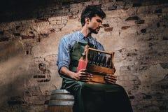 Brasseur fatigué dans le tablier se reposant sur un baril et des prises une boîte en bois avec de la bière de métier photos stock