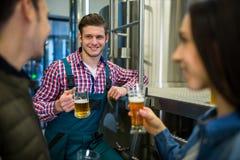 Brasseurs examinant la bière à l'usine de brasserie Images libres de droits