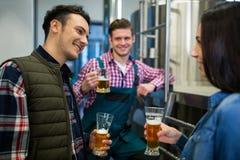 Brasseurs examinant la bière à l'usine de brasserie Image stock