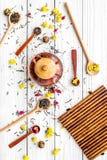 Brassez le thé aromatique Pot de thé près des cuillères en bois avec les feuilles de thé, les fleurs et les épices sèches sur le  photographie stock