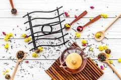 Brassez le thé aromatique Pot de thé près des cuillères en bois avec les feuilles de thé, les fleurs et les épices sèches sur le  photographie stock libre de droits