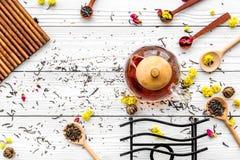 Brassez le thé aromatique Pot de thé près des cuillères en bois avec les feuilles de thé, les fleurs et les épices sèches sur le  image stock
