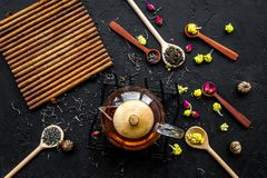 Brassez le thé aromatique Pot de thé près des cuillères en bois avec les feuilles de thé, les fleurs et les épices sèches sur le  photo stock