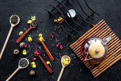 Brassez le thé aromatique Pot de thé près des cuillères en bois avec les feuilles de thé, les fleurs et les épices sèches sur le  photos libres de droits