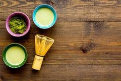 Brassez le thé vert de matcha Poudre de Matcha, thé prêt de matcha, batteur sur l'espace en bois foncé de copie de vue supérieure photo stock