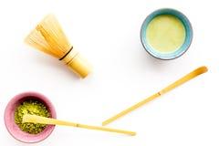 Brassez le thé vert de matcha Poudre de Matcha, thé prêt de matcha, batteur sur la vue supérieure de fond blanc photographie stock