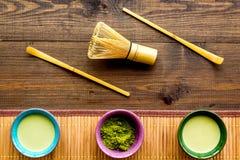 Brassez le thé vert de matcha Poudre de Matcha, thé prêt de matcha, batteur sur la vue supérieure de fond en bois foncé photographie stock