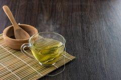 Brassez une tasse de thé vert avec le sac images stock