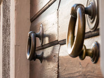 Brassy doorknob on wooden door, two handles Royalty Free Stock Photos